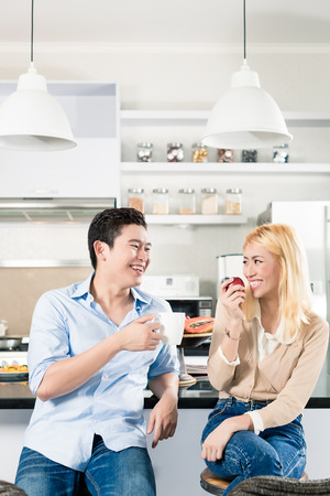 modern apartment: Asian couple having breakfast together in modern apartment