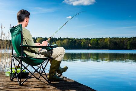 물에 가까운 부두에 앉아 호수에서 낚시하는 사람 (남자)