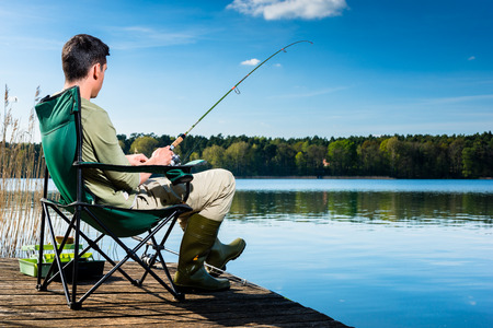 Homme de pêche au lac assis sur la jetée près de l'eau Banque d'images