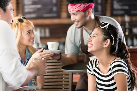 mujer tomando cafe: Camarero sirviendo caf� en caf� asi�tico para las mujeres y el hombre que ofrecen las bebidas en una bandeja Foto de archivo