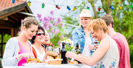 庭やグリルのパーティーでバーベキュー ソーセージと肉を食べている友人 写真素材