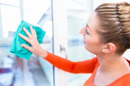 apartment cleaning: Woman cleaning window in her apartment Stock Photo