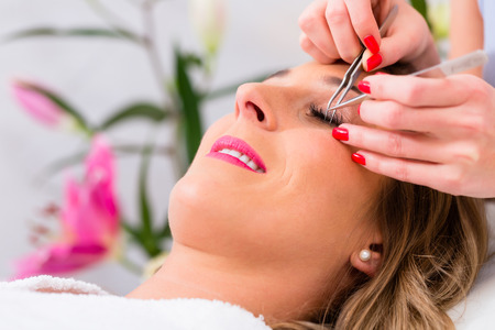 Woman receiving false eye lashes in beauty studio