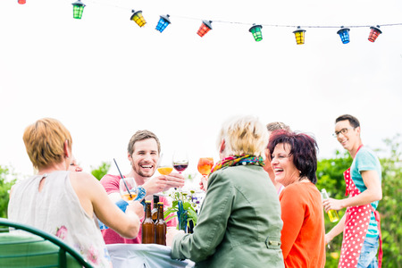 parrillero: Amigos y vecinos en la mesa larga que celebran tostado fiesta con bebidas