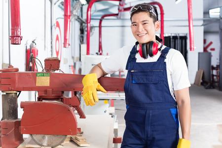 carpintero: Carpintero de Corea en el taller de madera con sierra mirando a la cámara