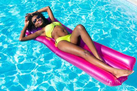 african american sexy: African woman swimming on air mattress in swimming pool in summer