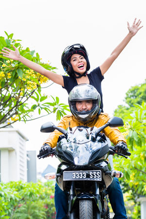 free riding: Indonesian woman feeling free on motorcycle stretching her arms out