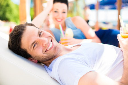 drinks on bar: Couple in beach bar relaxing with drinks