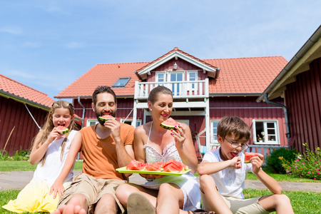 mom's house: Family sitting in grass front of home eating water melon Stock Photo