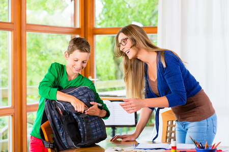 children school: Mother and son packing school bag for next day