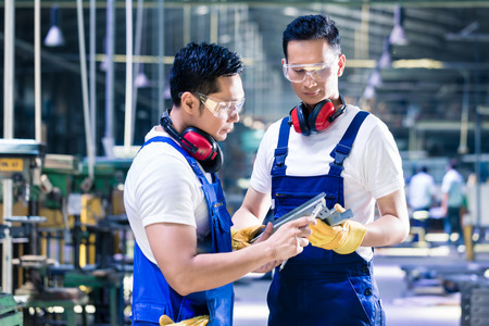 trabajadores: Personas asi�ticas del trabajador de la pieza de trabajo de comprobaci�n en la planta de producci�n de discutir las mediciones