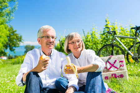 Senior couple eating fruit and drinking at picnic in summer, beautiful landscape in the background photo