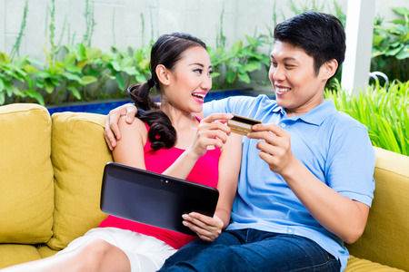 married together: Asian couple shopping online in internet with laptop and credit card