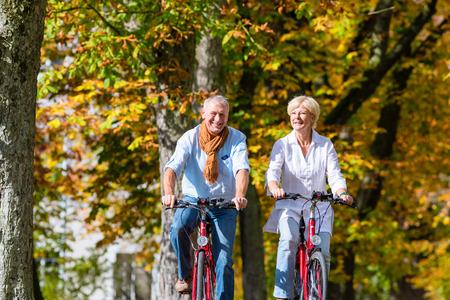Starší pár, muž a žena, na kolech, které mají na kole turné v parku na podzim