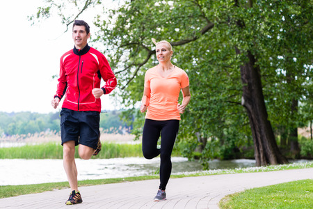 dirt path: Woman and man jogging on dirt path in the woods together