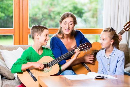 jugando: Familia que hace música en el país con la guitarra, madre, hija e hijo jugando