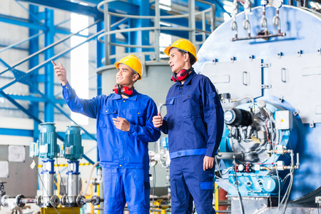 Industrial workers: Worker in Asian manufacturing plant discussing in front of machines Stock Photo