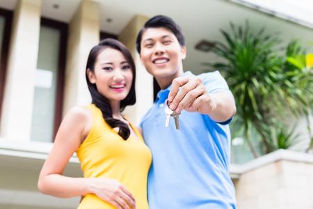 Chinesisches Ehepaar, Frau und Mann, zeigt Schlüssel zu ihrem neuen Haus sich in Standard-Bild - 44548919