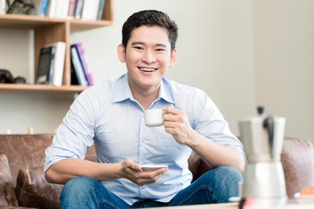 tomando café: Café de consumición del hombre japonés en su sala de estar