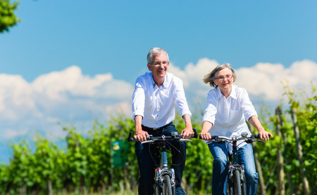 senior men: Senior woman and man using bike in summer in vineyard Stock Photo