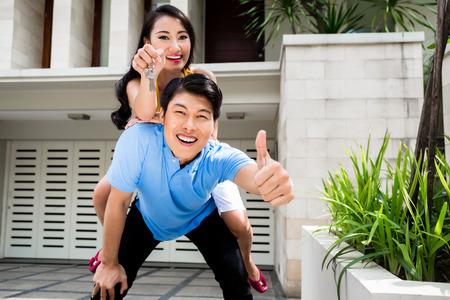 Chinesische Frau und Mann, die das neue Haus genießen, kauften sie die Daumen hoch Standard-Bild - 44549782