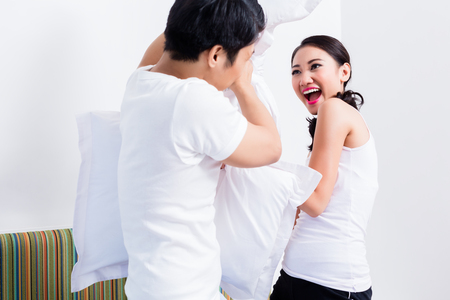 pillow fight: Chinese Woman and man having pillow fight