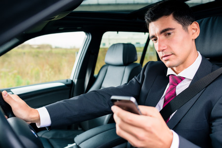 business man phone: Man texting on his phone while driving by car Stock Photo