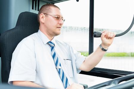 servicios publicos: El conductor del autobús que hace el aviso usando el micrófono