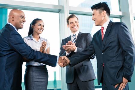 INTERNATIONAL BUSINESS: Negocios apretón de manos en el sublime oficina con vista a la ciudad, un acuerdo es alcanzado