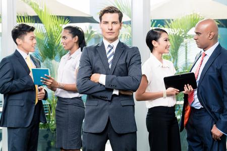 negocios internacionales: Reunión del equipo de negocios con el hombre mirando al frente de cámara, en el pueblo de fondo de diversas etnias discutir