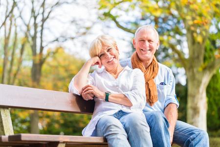 tercera edad: Superior de la mujer y el hombre sentado en el banco participa en otoño