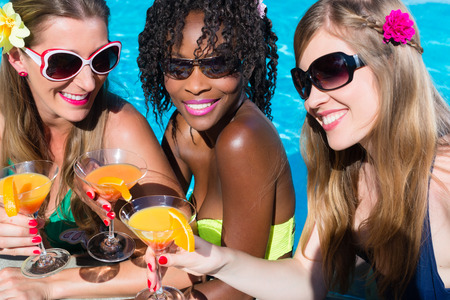 african bikini: Three women friends drinking cocktails in swimming pool bar, African and Caucasian girls