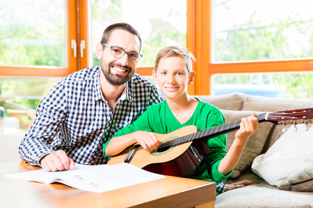 making music: Father and son playing guitar at home, making music together
