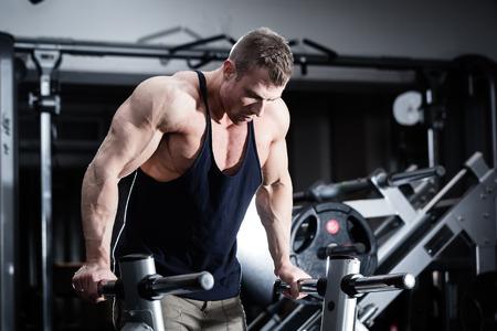 dips: Bodybuilder man in gym doing dips as arm training Stock Photo
