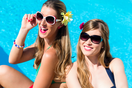 bikini pool: Girl friends tanning at swimming pool in the sun in front of the water leaning against each other