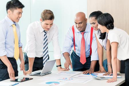 diversidad: Equipo de negocios de Asia en reunión de estrategia inclinándose sobre el escritorio de nuevo con gráficos y números Foto de archivo