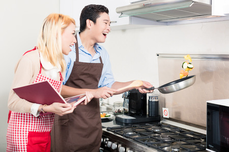 pan asian: Asian couple cooking vegetables in frying pan Stock Photo