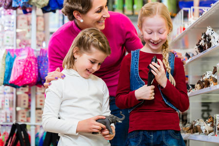niños de compras: Familia compra de juguetes en la tienda de juguetes en la juguetería de pie en figuras choosing estantería Foto de archivo