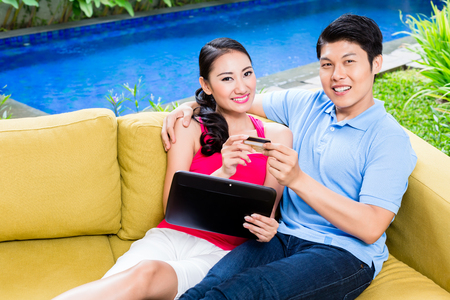room card: Asian couple shopping online in internet with laptop and credit card