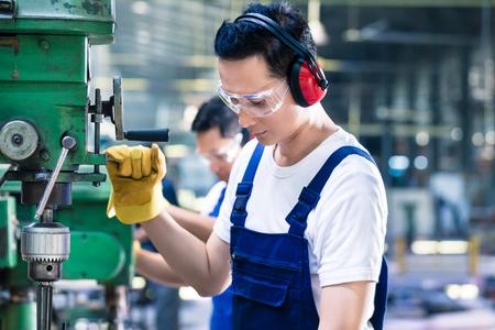 Asiatische Arbeiter im Produktionswerk Bohrungen auf Maschine in der Fabrikhalle Standard-Bild - 44550725