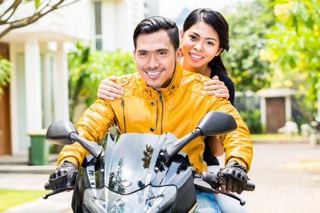 yellow jacket: Asian couple riding motorcycle, wife is sitting behind her husband
