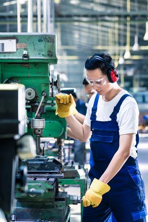 工場フロアのマシンで掘削生産工場でアジア人労働者