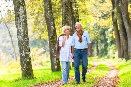 Ältere Frau und ein Mann, ein Paar, umarmen einander, die Weg im Herbst Wald