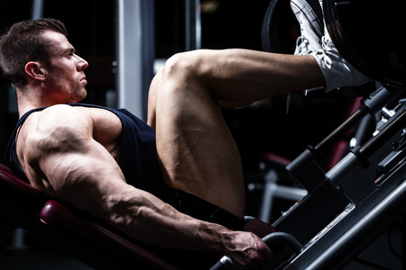 piernas hombre: Hombre en el entrenamiento de gimnasia en prensa de piernas para definir sus m�sculos superiores de la pierna Foto de archivo