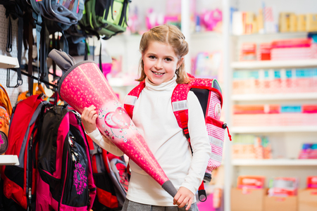 first day: Schoolgirl with traditional first day cone in school in store