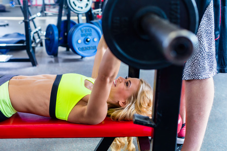 trainers: Woman with personal trainer at bench press in gym exercising for better fitness