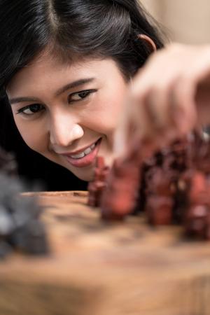 indonesian woman: Indonesian woman playing chess setting figure