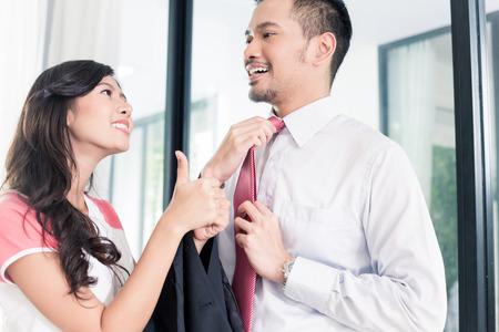 Esposas: Esposa ayudar a su hombre de ir a la oficina para el trabajo vinculante su corbata de buen atuendo