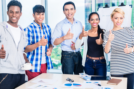 founder: Successful business team in kickoff meeting with flipchart and graphs on the table, international diversity setting Stock Photo
