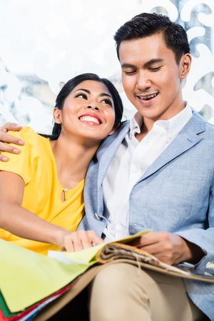 furniture store: Asian couple buying sofa in furniture store, sitting on couch choosing color and material